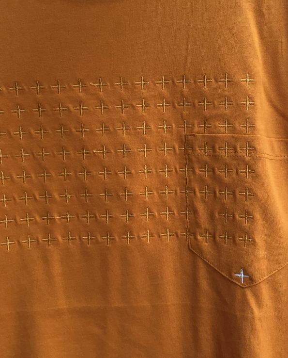 Detalle de bordado sobre camiseta de color mostaza