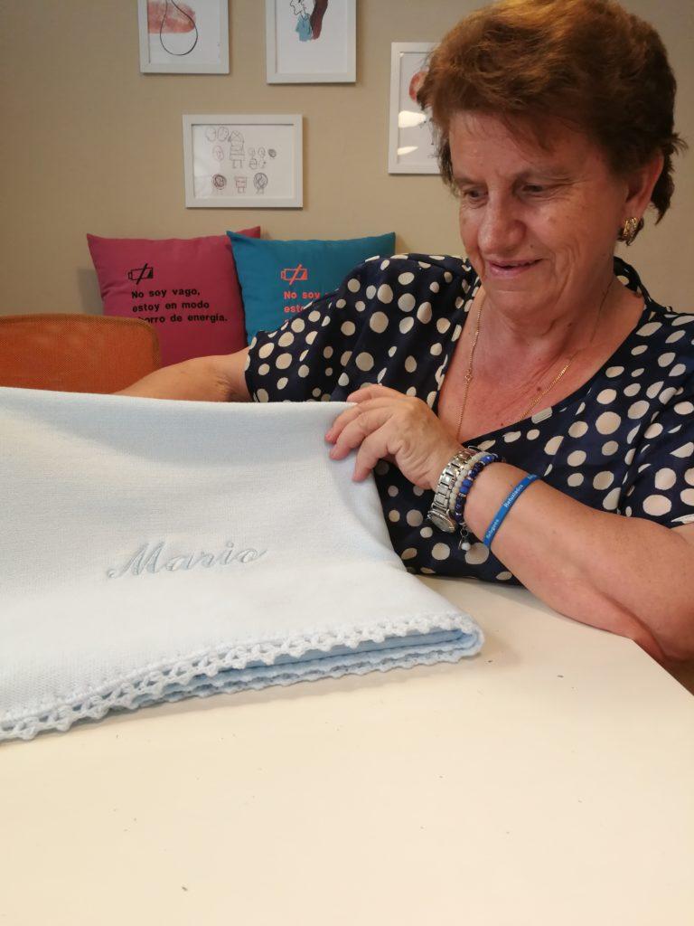 María Leal enseñando una de sus mantitas de punto personalizadas